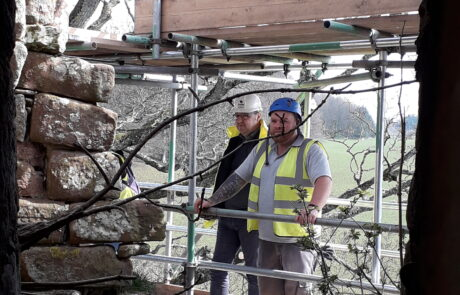 Image of two people standing on scaffolding looking at stonework