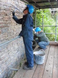 Image of volunteers on scaffolding restoring a stone wall