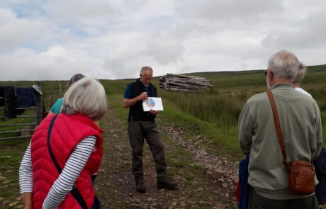 Image of man standing on hillside showing a drawing to a man and a woman who have their backs to the camera
