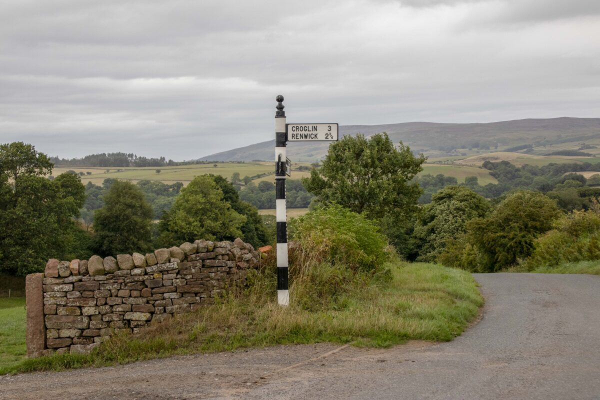 Image of old black and white fingerpost sign with hills behind