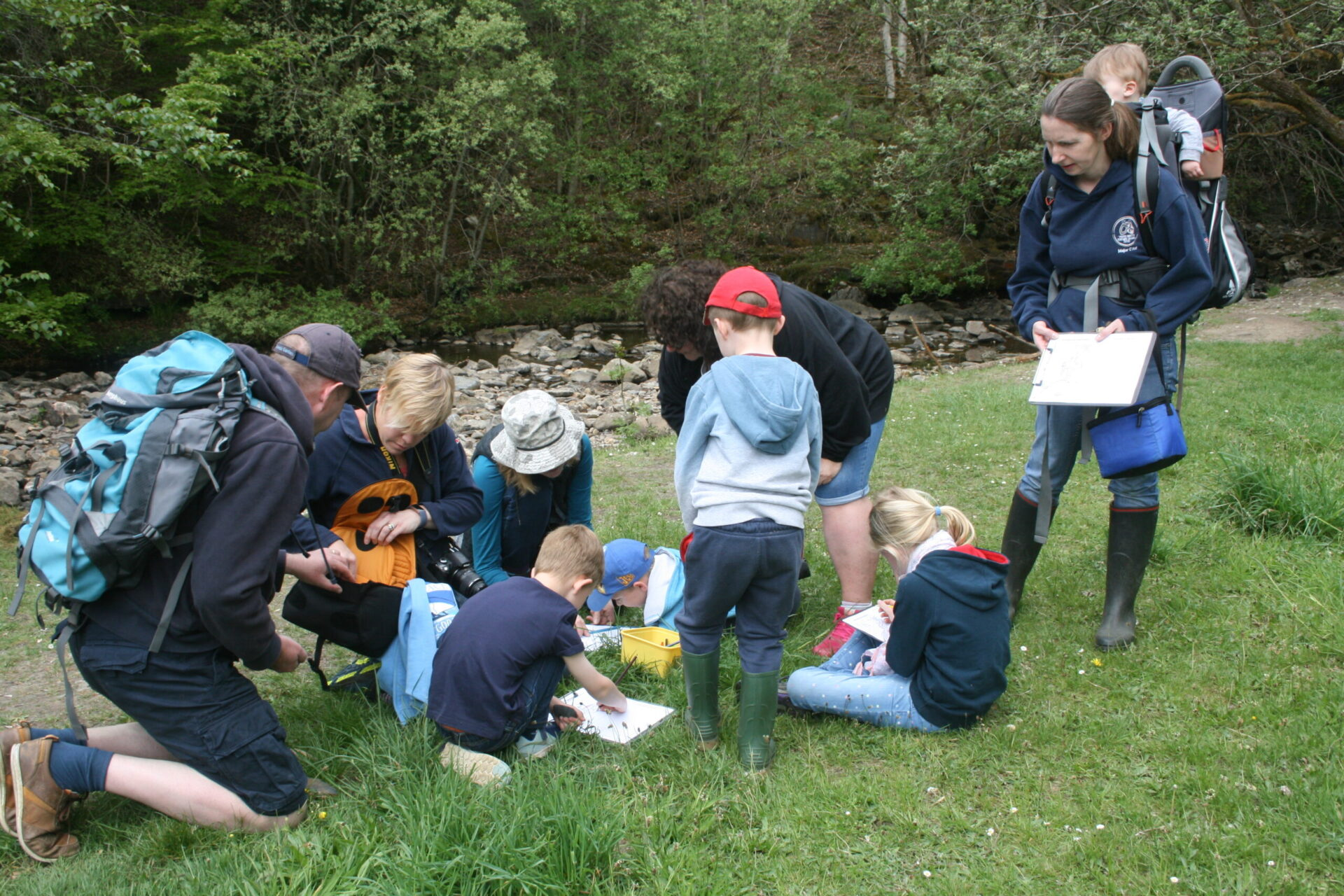 Image of group of adults and children working on a project in a field