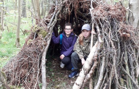 Image of two children sitting inside a shelter made from tree branches