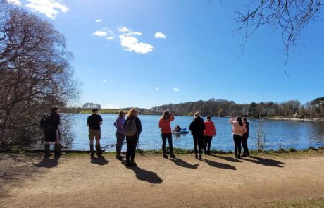 Image of group standing by a lake in sunshine with a blue sky