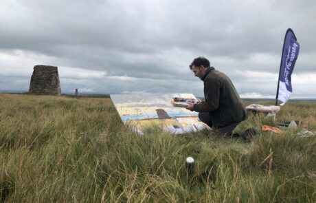 Picture of man sitting outside sketching