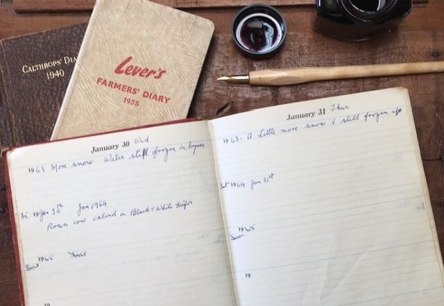 Image of an open diary with an ink pen, a closed Farmer's diary and an ink pot