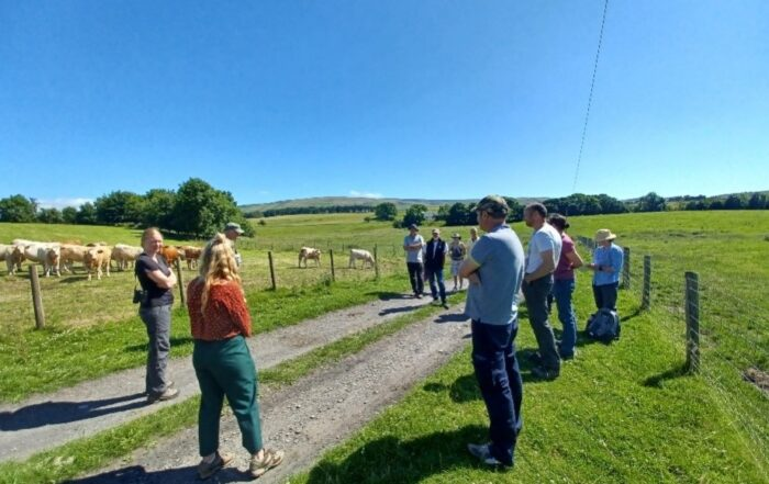 Photo of group of people standing talking on a farm track