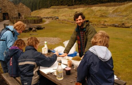 Photo of group around a table outside drawing and painting
