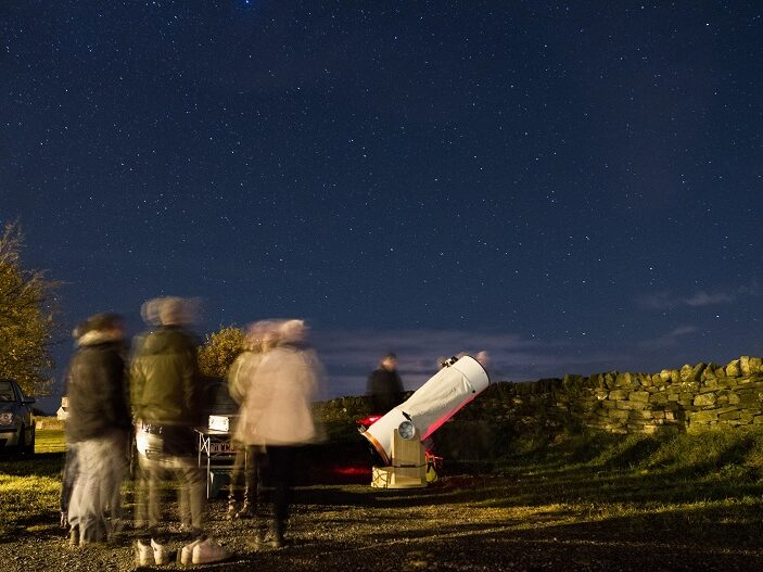 Image of people outside at night standing near large telescope