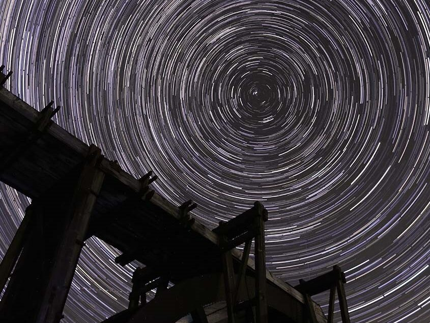 Image of star trails against dark sky with silhouette of mine machinery